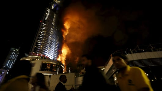 People run away after the burning The Address Hotel in downtown Dubai in the United Arab Emirates on Dec. 31, 2015.